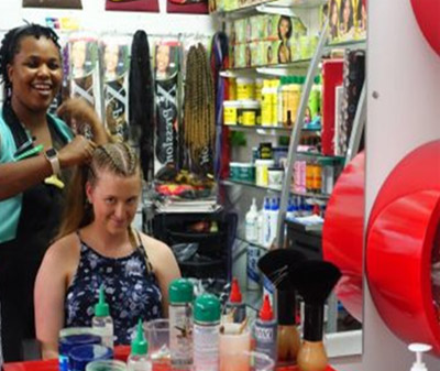 A Migrant woman African Entrepreneur does the hair of a client in her hair salon.