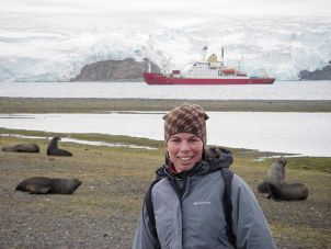Jan Strugnell in the Antarctic with the ship James Clark Ross in the background