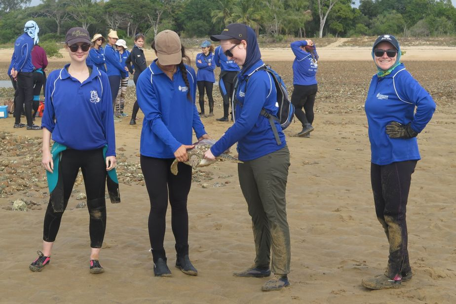 Four women wearing SunSmart clothing on a beach, two are holding a turtle between them