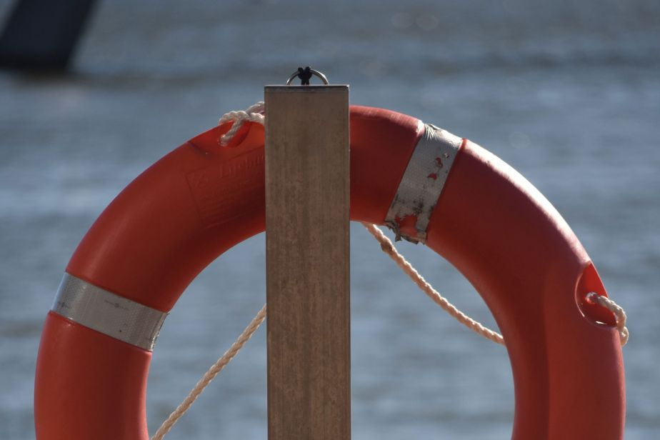 a life buoy on a post, water in background