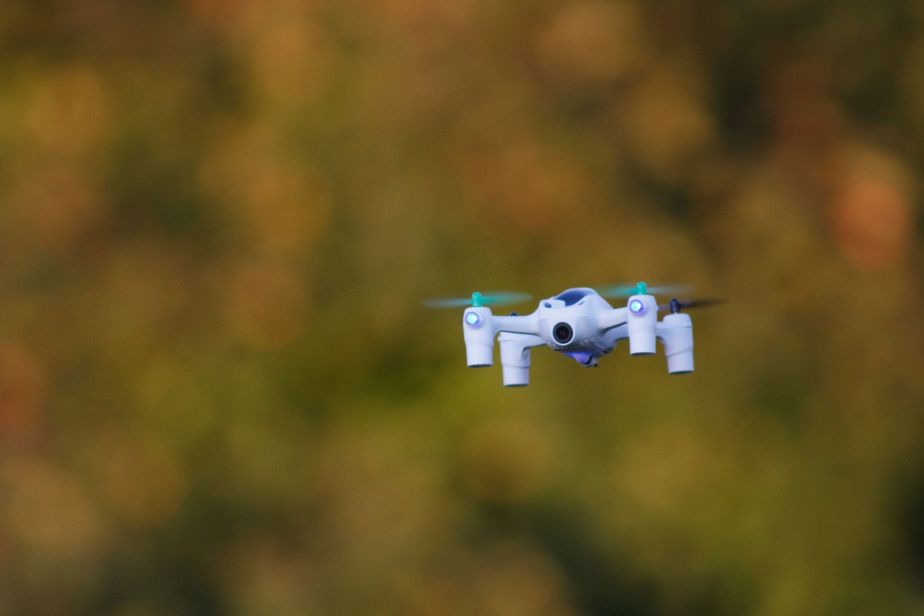 A small white drone in focus with a blurred background of orange tones