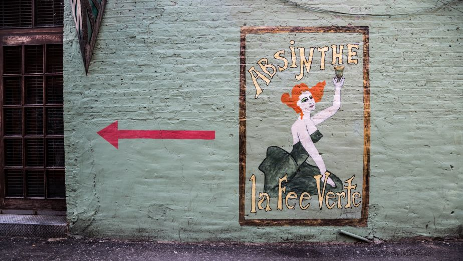 Absinthe mural on a grey wall, large red arrow pointing left