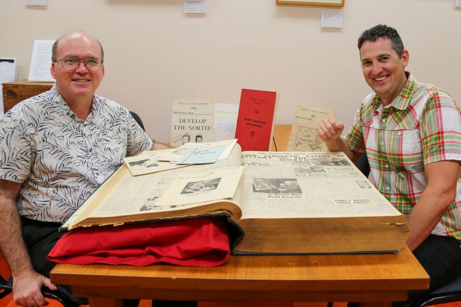 Two men, one on either side of a large bound collection of newspapers