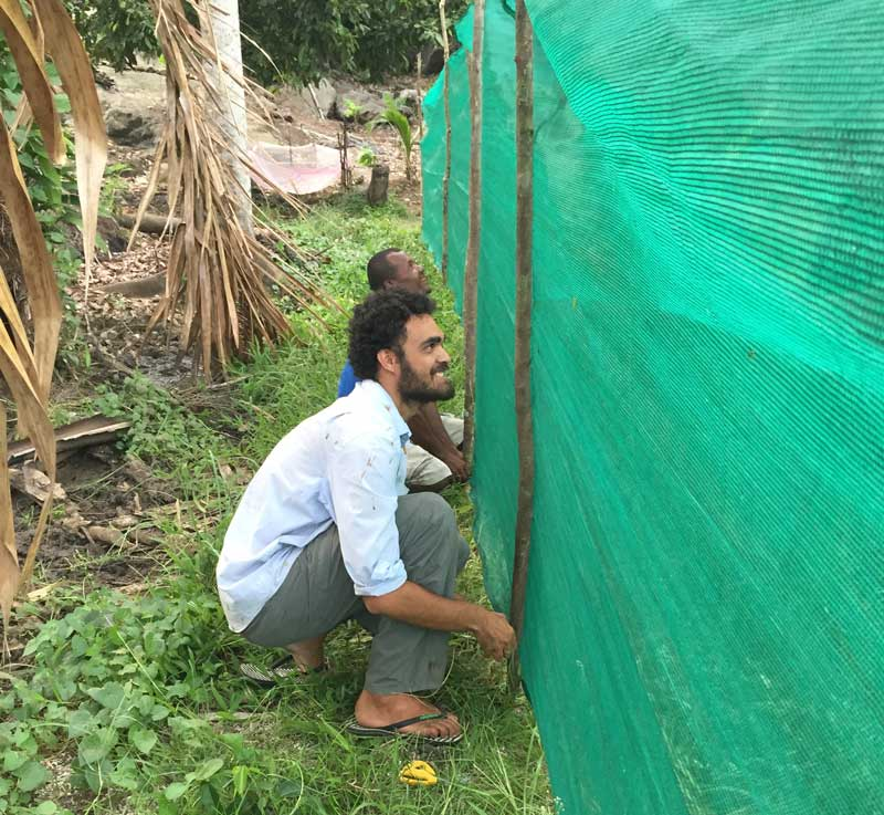 Edgar helping set up a mosquito net outdoors in the Solomon Islands.